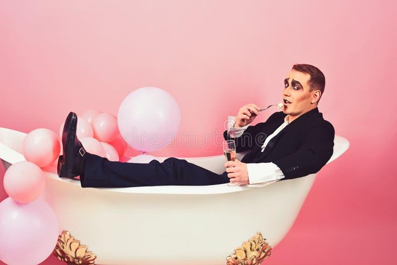 Baño y relajación Imite al actor gozan el bañarse en tina de baño Imite al hombre tiene partido de la celebración con la comida y imagenes de archivo