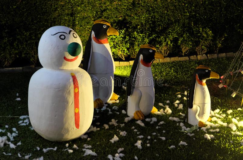 Bałwan i trzy złego pingwinu stoimy na zielonym gazonie Bałwan z zielonym nosem Bożenarodzeniowy świętowanie w krajach z zdjęcie royalty free
