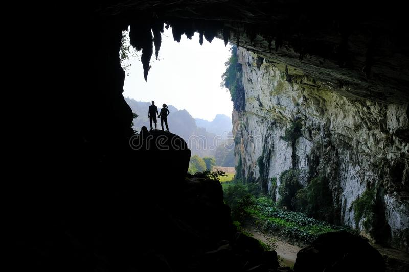 Ba Be Lakes / Vietnam, 03/11/2017: Silhouettes of two people standing in a rocky outcrop inside a giant cave in the North stock photo