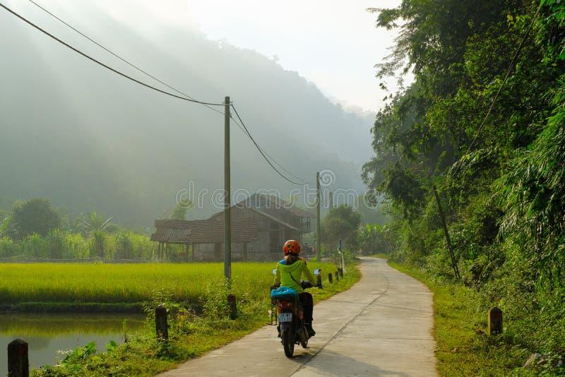 Ba ist Seen/Vietnam, 04/11/2017: Motorbiking-Wanderer, der Reispaddys und lokale Häuser auf einer Straße während des Sonnenaufgan lizenzfreie stockfotos