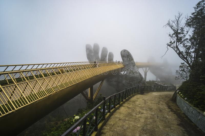 Ba Na Hill mountain resort, Danang city, Vietnam. The Golden Bridge is lifted by two giant hands in the tourist resort on Ba Na. Hill in a foggy day at Danang stock image
