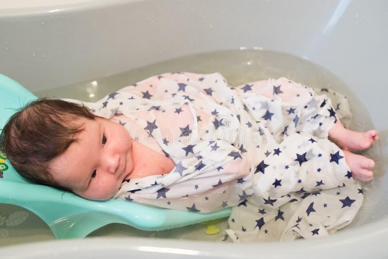 Ba?o de un beb? baña a su hijo en un pequeño baño plástico imágenes de archivo libres de regalías