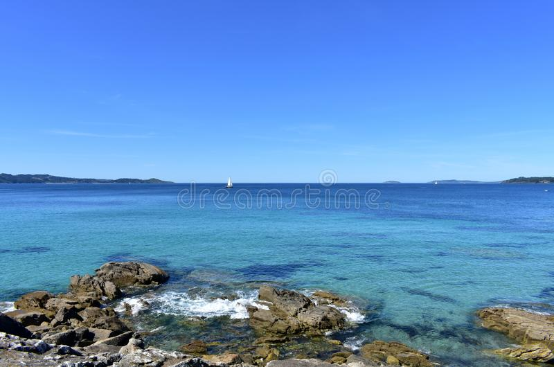 Baai met rotsen, varende boten en blauwe hemel r royalty-vrije stock afbeelding
