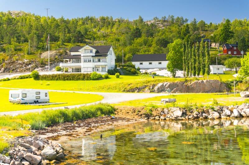 Baai op het Noorse platteland, landelijke huizen op de kust stock foto's