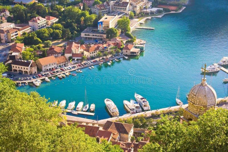 Baai van Kotor in Montenegro met mening van bergen, boten en oude huizen met rode tegeldaken stock foto