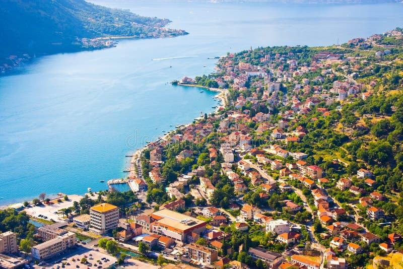 Baai van Kotor in Montenegro met mening van bergen, boten en oude huizen met rode tegeldaken stock afbeelding