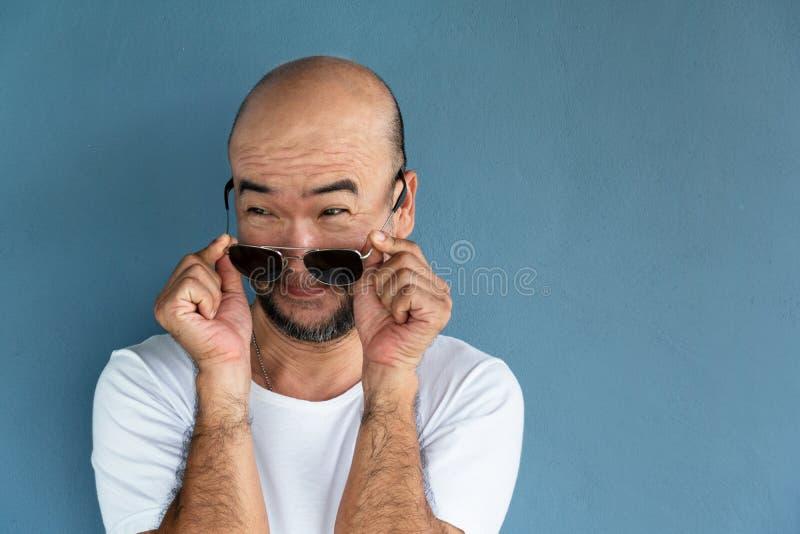 Baard kale Japanse mens in grappige uitdrukking met zonnebril in witte toevallige T-shirt op blauwe concrete achtergrond stock fotografie