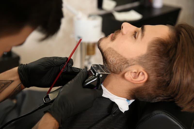 Baard van de kapper de in orde makende cliënt in herenkapper royalty-vrije stock fotografie