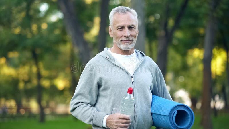 Baardgrootvader in de yogamat van de sportkledingsholding en fles water, gezondheid royalty-vrije stock fotografie