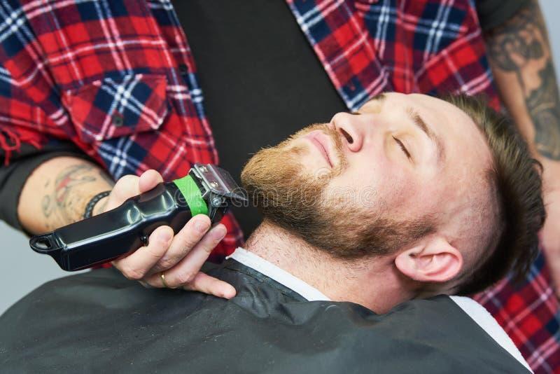Baardzorg mens terwijl het in orde maken van zijn gezichtsdiehaar bij de herenkapper wordt gesneden royalty-vrije stock foto