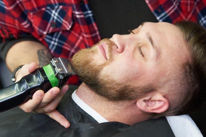 Baardzorg mens terwijl het in orde maken van zijn gezichtsdiehaar bij de herenkapper wordt gesneden royalty-vrije stock afbeelding