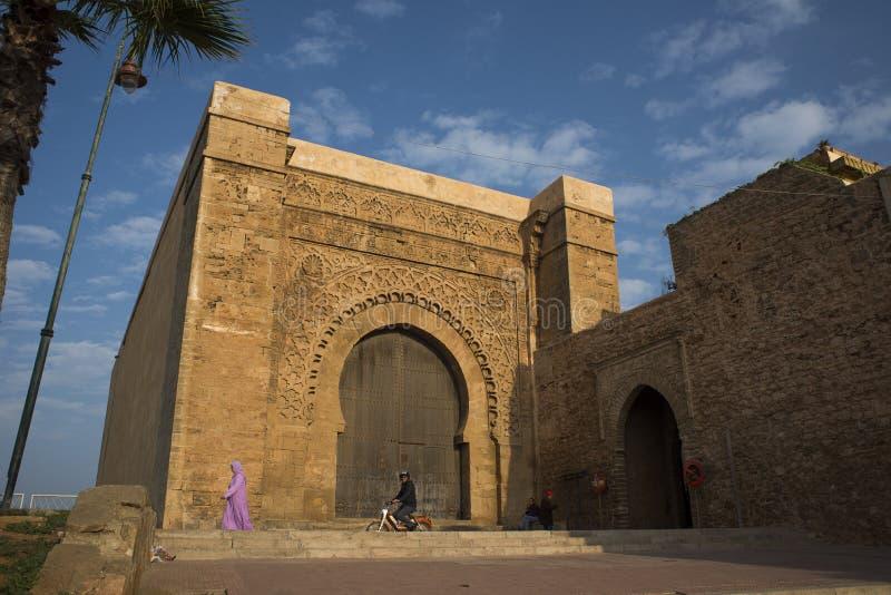 Bab el Kebir gate of Kasbah of the Udayas. Rabat, Morocco - December 11, 2015: People with djellaba walking in fron of Bab el Kebir. Main gate of Kasbah of the stock photography