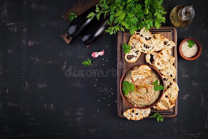 Baba ghanoush vegan hummus from eggplant with seasoning, parsley and toasts. stock image