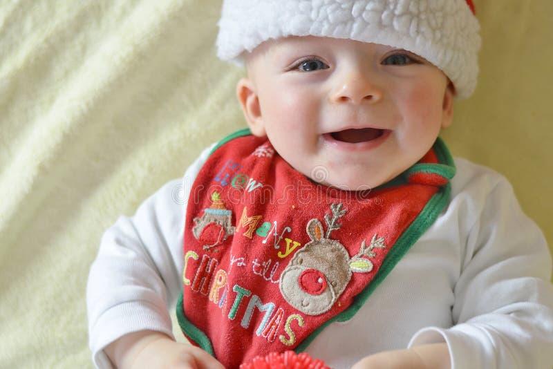 Babador e tampão vestindo de sorriso do Natal do bebê imagens de stock