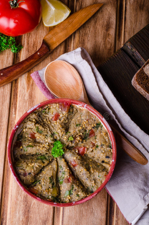 Babaganoush with tomatoes, cucumber and parsley - arabian eggplant dish or salad on wooden background. Selective focus royalty free stock image