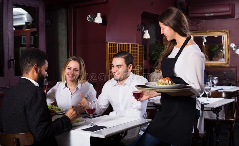 Babbelende volwassenen en vrolijke serveerster royalty-vrije stock afbeelding