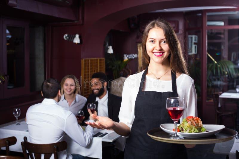 Babbelende volwassenen en vrolijke serveerster royalty-vrije stock foto