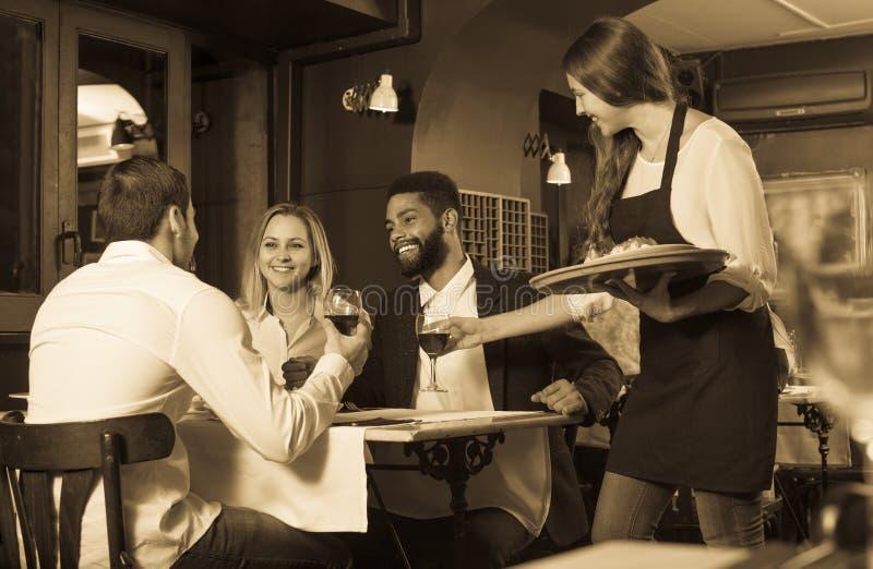 Babbelende volwassenen en vrolijke serveerster stock afbeelding