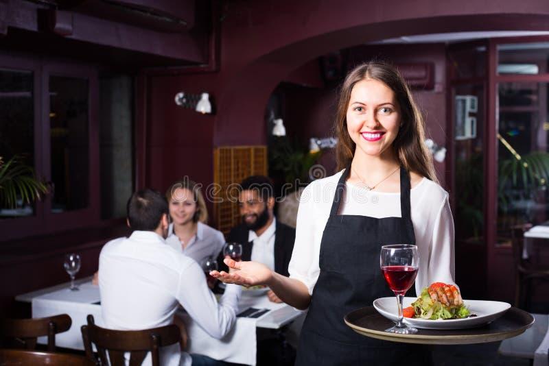 Babbelende volwassenen en vrolijke serveerster stock foto's