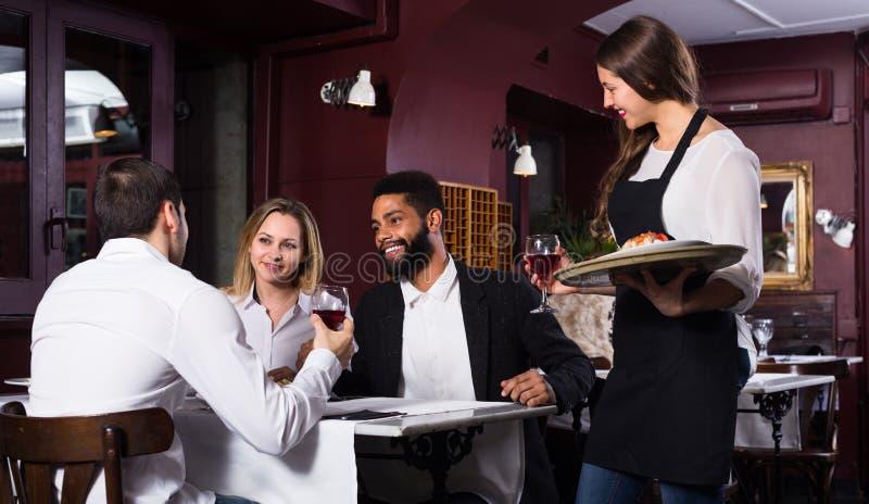 Babbelende volwassenen en vrolijke serveerster royalty-vrije stock foto's