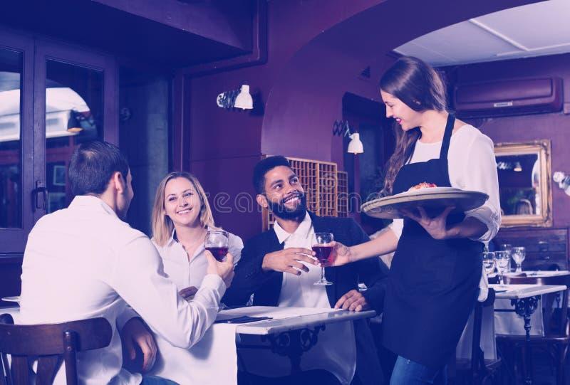 Babbelende volwassenen en vrolijke serveerster royalty-vrije stock fotografie