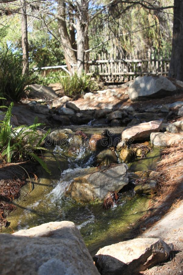 Babbling brook by a rustic bridge. Taken at animal park in mountainous desert and forest stock image