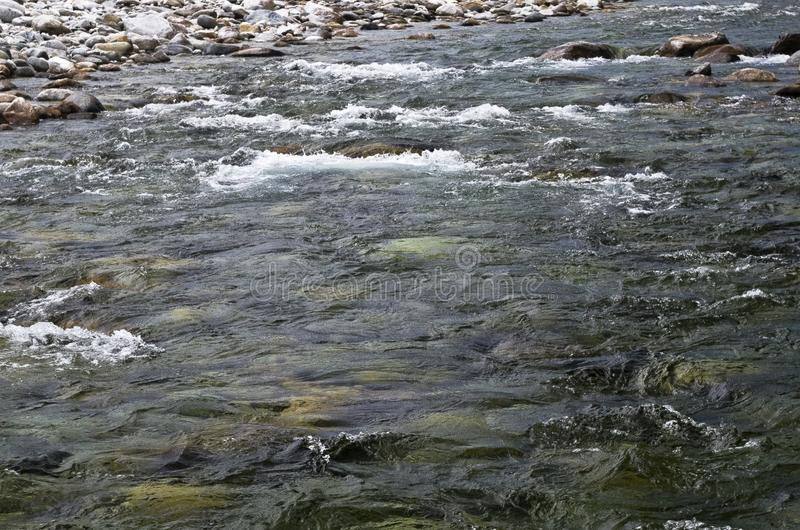 Babbling stream. Fresh water runoff between the valley mountains. glacial snow melt unpolluted Plätschernder Strom royalty free stock images