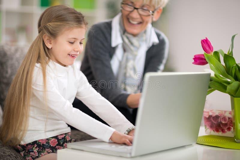 Babci dopatrywania wnuczka używa laptop fotografia royalty free