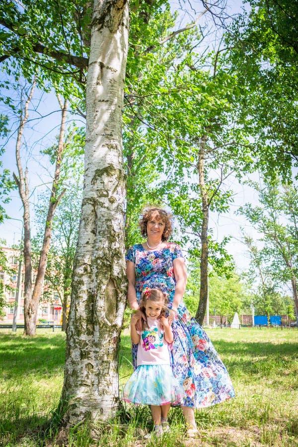 Babci i wnuczki uścisk i sztuka, stojak w lesie blisko brzozy zdjęcia royalty free