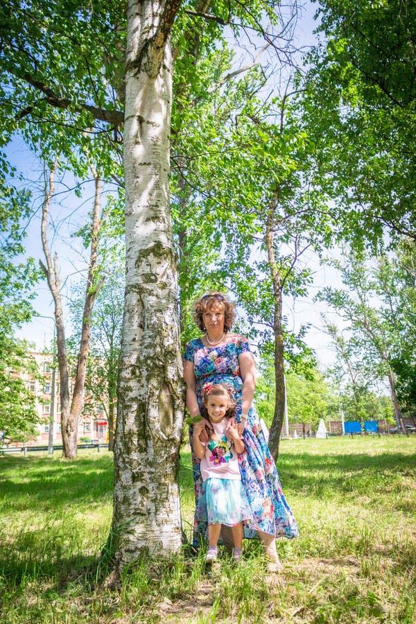 Babci i wnuczki uścisk i sztuka, stojak w lesie blisko brzozy zdjęcia stock