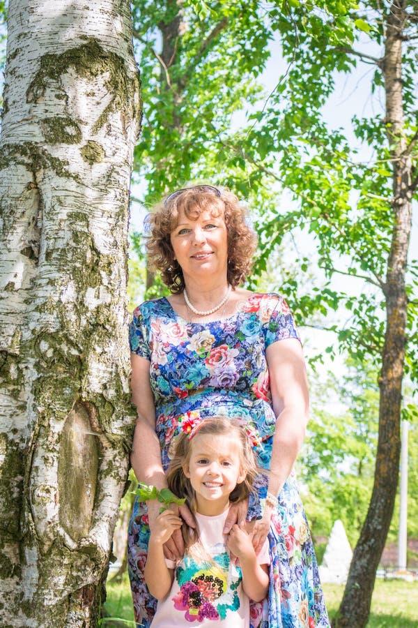 Babci i wnuczki uścisk i sztuka, stojak w lesie blisko brzozy obrazy stock