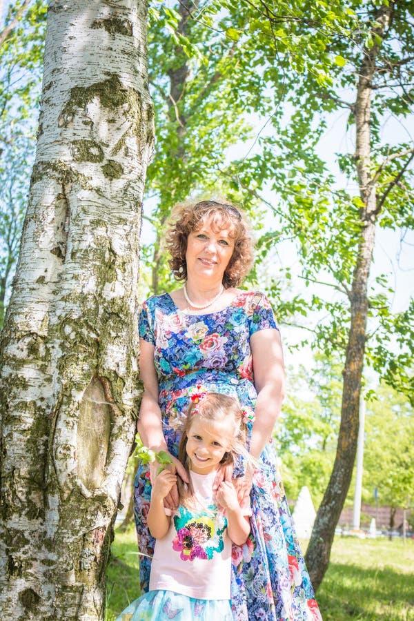 Babci i wnuczki uścisk i sztuka, stojak w lesie blisko brzozy zdjęcie royalty free