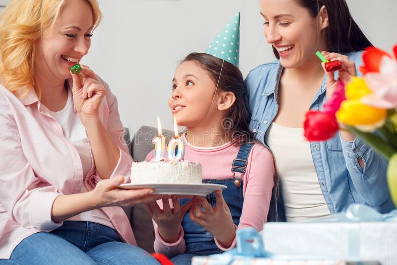 Babci matka i córki wpólnie w domu dziewczyny mienia urodzinowy siedzący tort ono uśmiecha się w górę zdjęcia stock