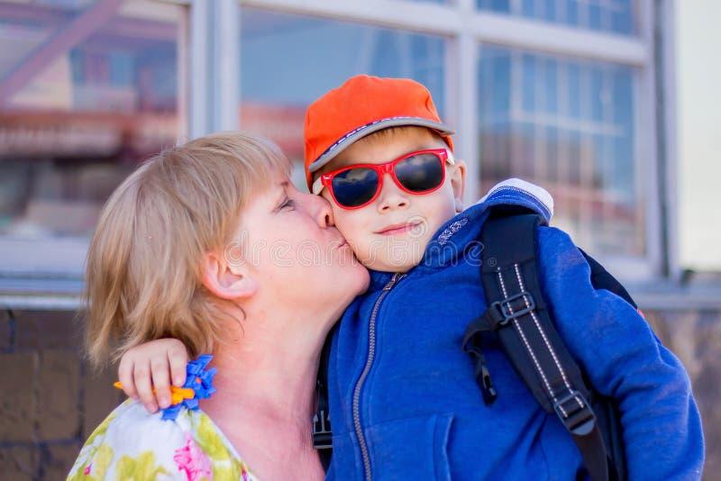 Babcia całuje jej wnuka Modna ubierająca chłopiec z grandm obraz stock