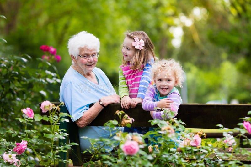 Babcia i dzieciaki siedzi w ogródzie różanym zdjęcia stock