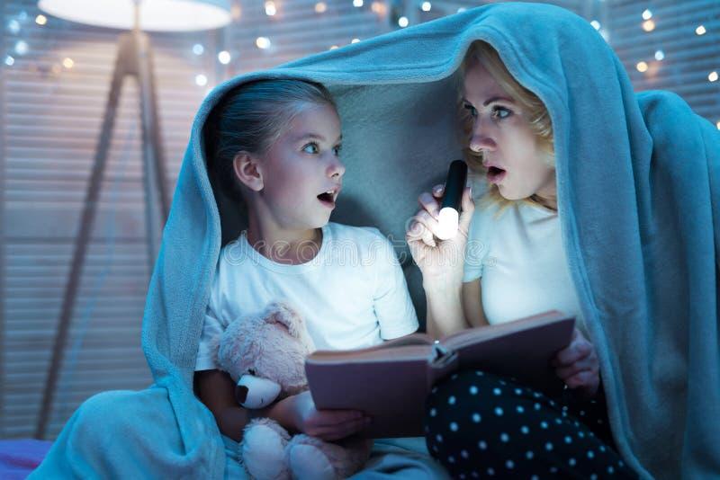 Babcia i wnuczka jesteśmy czytelniczym książką z latarką pod koc przy nocą w domu zdjęcia stock