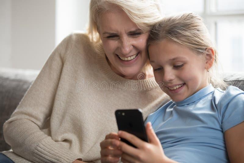 Babcia i wnuczka ma zabawę w internecie używać smartphone obraz royalty free