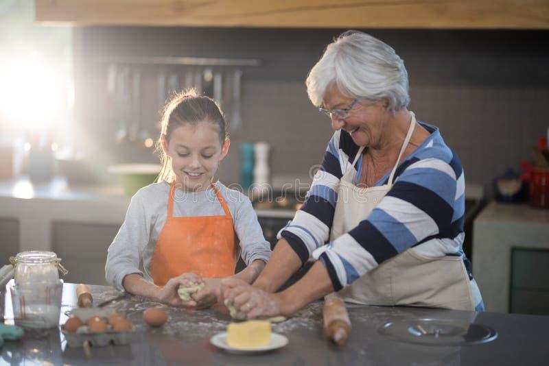 Babcia i wnuczka ugniata ciasto zdjęcie royalty free