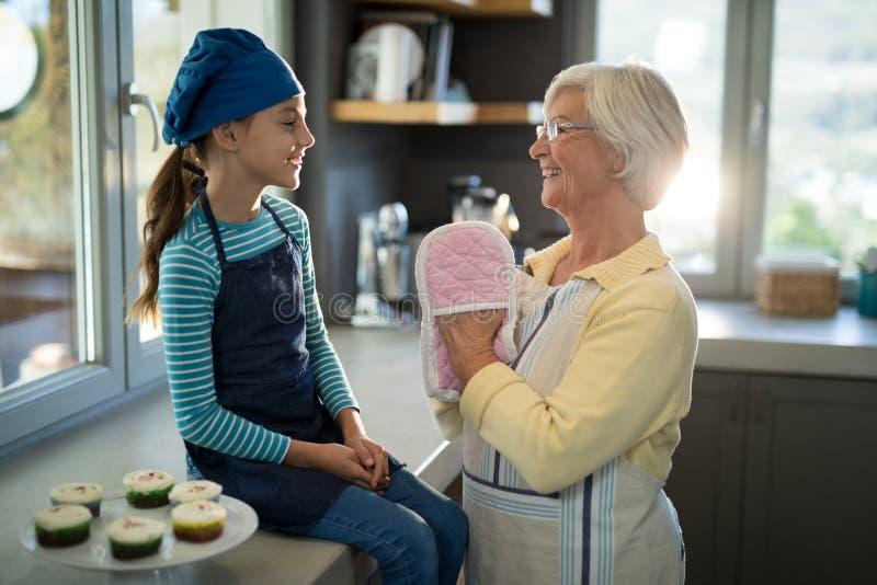 Babcia i wnuczka z piekarnik rękawiczkami w kuchni obraz stock