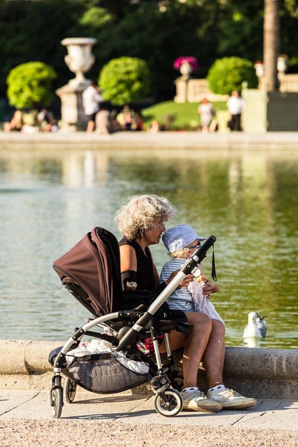 Babcia i wnuk karmimy ptaki w Luksemburg ogródzie zdjęcia stock