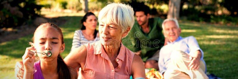 Babcia patrzeje jej wnuczki dmuchanie gulgocze w parku zdjęcia stock