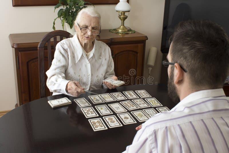 Babcia stawia tarot wnuka Pełnoletnia czarodziejka stawia tarot karty zdjęcia stock