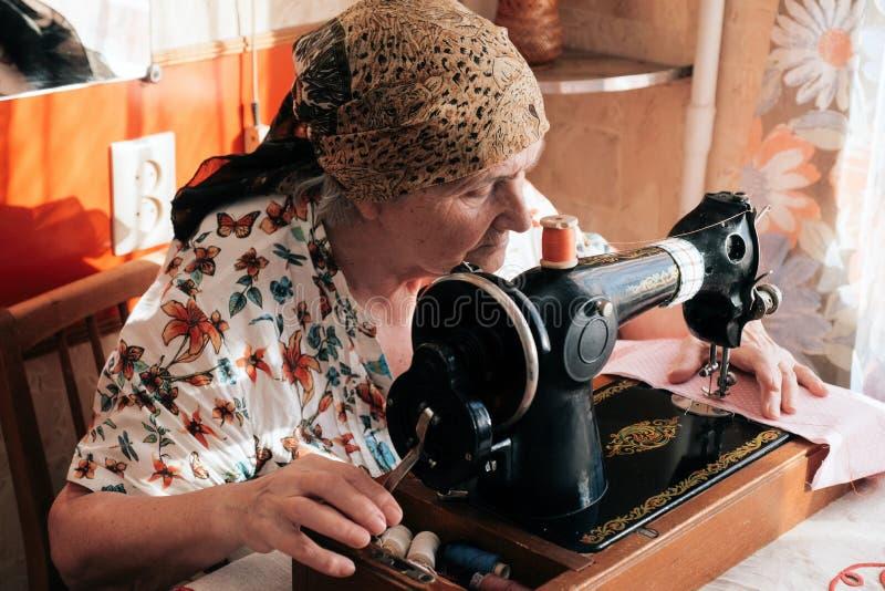 Babcia szy na rocznik szwalnej maszynie, ona ręki pcha różową tkaninę obraz stock