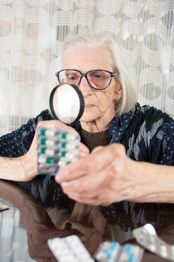 Babcia używa powiększać - szkło ustalać pigułki imię fotografia royalty free