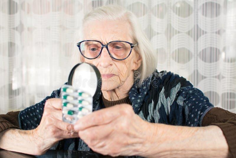 Babcia używa powiększać - szkło ustalać pigułki imię obrazy stock