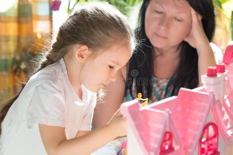 Babcia z śliczną małą dziewczynką bawić się w domu zarygluj składu pojęcia rodziny orzechy fotografia royalty free
