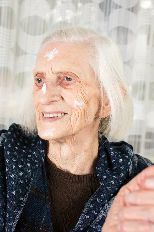 Babcia z twarzy śmietanki zakończeniem up obrazy stock