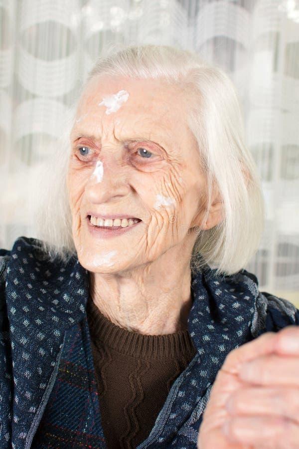 Babcia z twarzy śmietanki zakończeniem up obraz stock