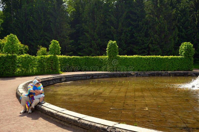 Babcia z wnukiem siedzi o fontannie w parku zdjęcie royalty free