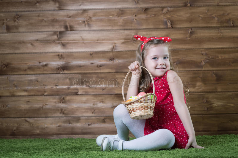 Babe collect Easter eggs. In a basket royalty free stock image